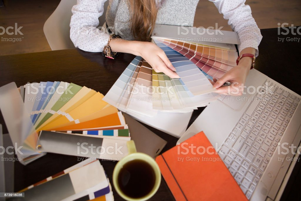 Creative people workplace. the young woman the designer holds color palette at office desk. stock photo