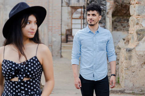 Hispanic young man smiling looking at the horizon with his girlfriend in front out of focus - distanced couple