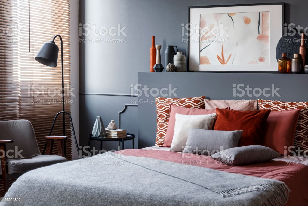 Creative poster on black bedhead above cozy bed with decorative cushions and gray blanket in bedroom interior with metal lamp and vintage armchair. Real photo zbiór zdjęć royalty-free