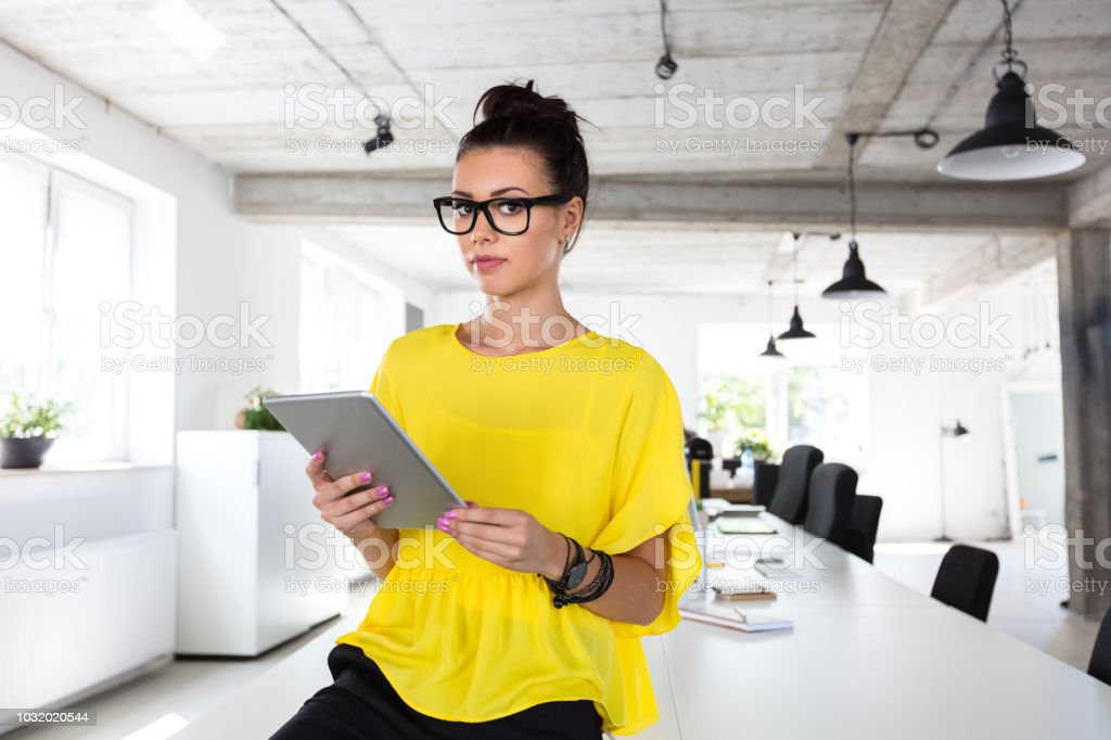 Creative professional with digital tablet in modern office Portrait of attractive young woman standing at a table with digital tablet. Creative professional with digital tablet in modern office. 20-24 Years Stock Photo