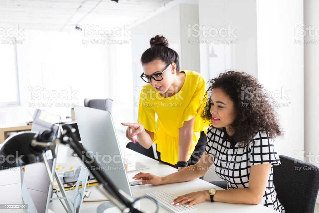 Creative professionals working together on computer stock photo