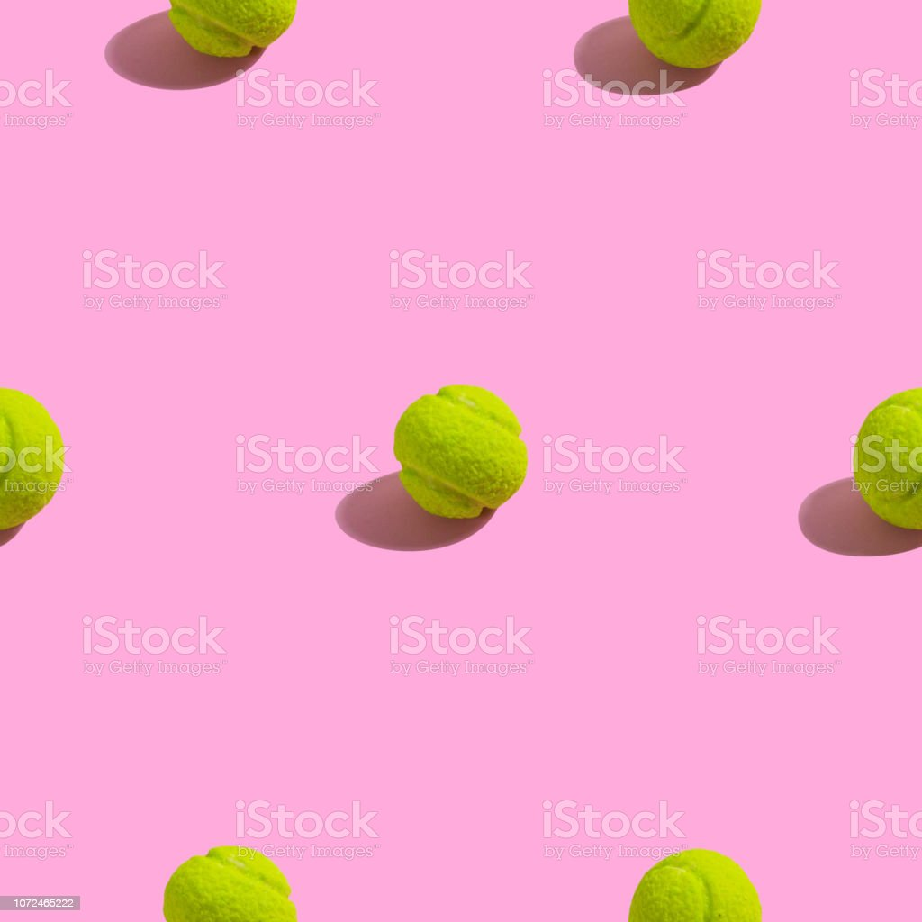 Creative seamless pattern with green tennis ball on pink background....