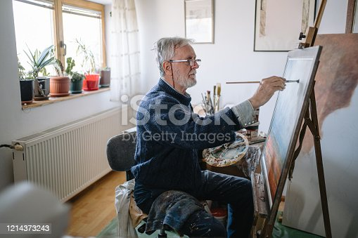 Inspired senior man painting in an art studio at home.