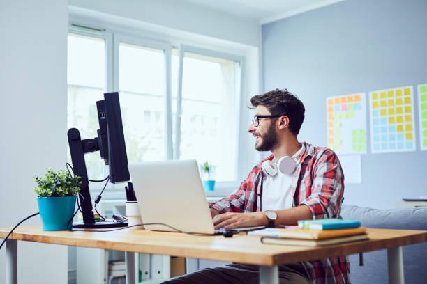 Kreativ lächelnd junger Mann, der an seinem Start-up-Geschäft im gemütlichen Home Office arbeitet – Foto