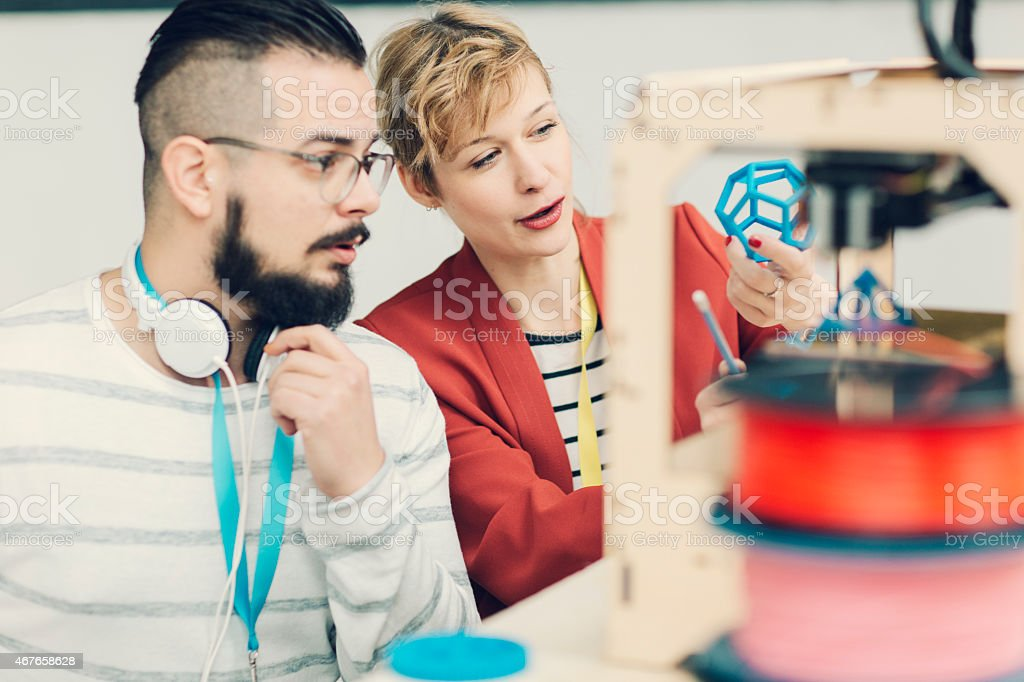 Creative Start-Up Business Team Working by 3D Printer. stock photo