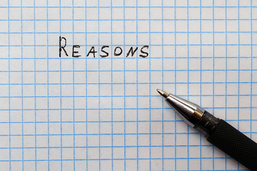 Pen inscription: Reasons on a sheet of squared notebook, background