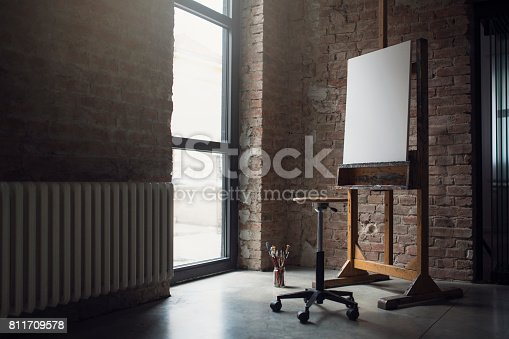 White canvas on painting easel, stool and paintbrushes in an artistic studio.