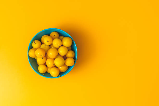Creative summer pattern made of fresh yellow cherry plums in blue bowl on pastel yellow background. Fruit minimal concept. Flat lay. stock photo