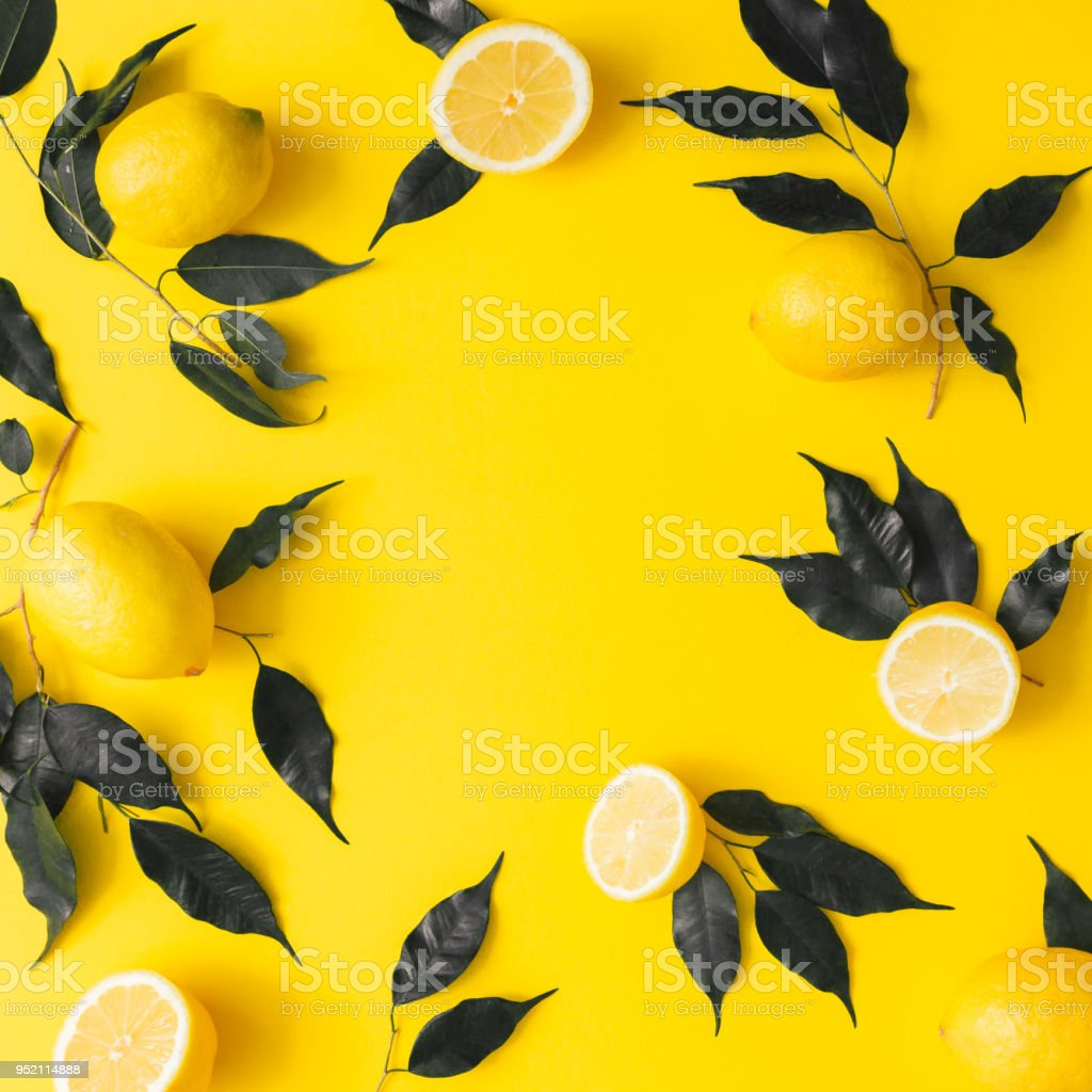 Creative summer pattern made of lemons and black leaves on yellow background. Fruit minimal concept. Flat lay. stock photo