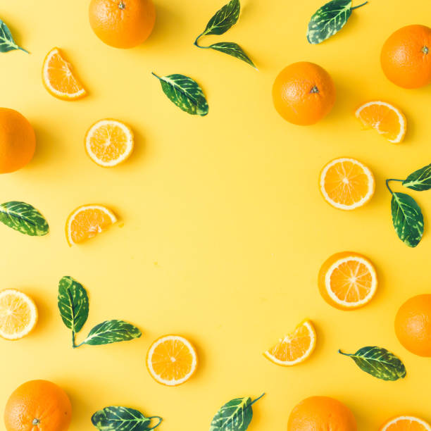 Creative summer pattern made of oranges and green leaves on pastel yellow background. Fruit minimal concept. Flat lay. stock photo