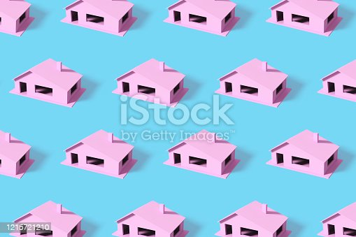 Creative summer pattern made with pink houses on blue background. Minimal summer concept.
