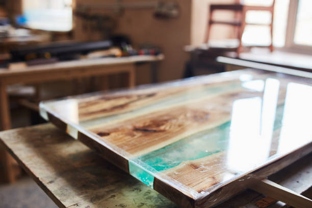 Creative table top with blue glass View of handmade wooden table top with epoxy resin element in lacquer on table in joinery shop lacquered stock pictures, royalty-free photos & images