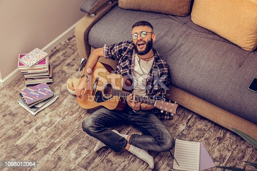 istock Creative talented musician playing the guitar at home 1098012064