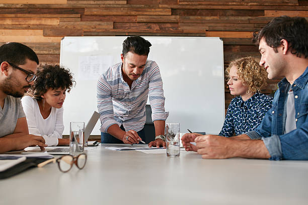 Equipo creativo hablando nuevas ideas sobre la mesa - foto de stock