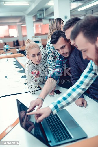 1083251186istockphoto Creative Team in a Textile Factory Working on Laptop 947415314