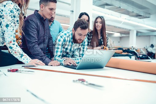 1083251186istockphoto Creative Team in a Textile Factory Working on Laptop 947417976