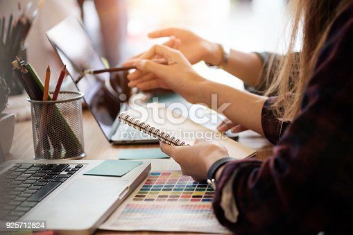 Creative team two woman working with computer in modern office, selective hands hold notebook paper.