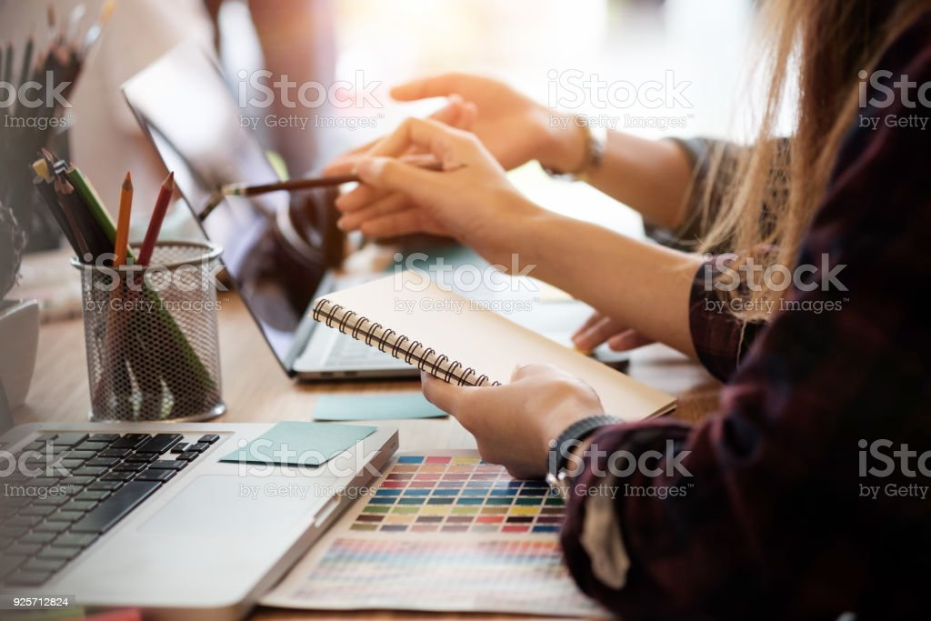 Creative team two woman working with computer in modern office, selective hands hold notebook paper. stock photo
