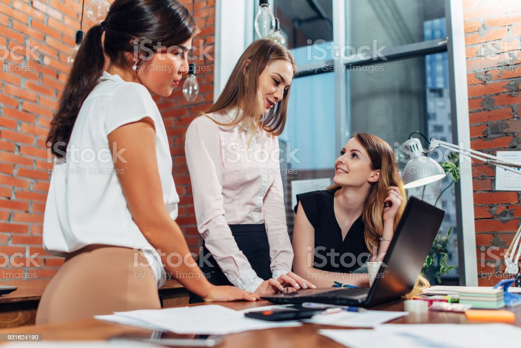 Creative team working on new project together looking and listening to their partner standing around desk using portable computer stock photo