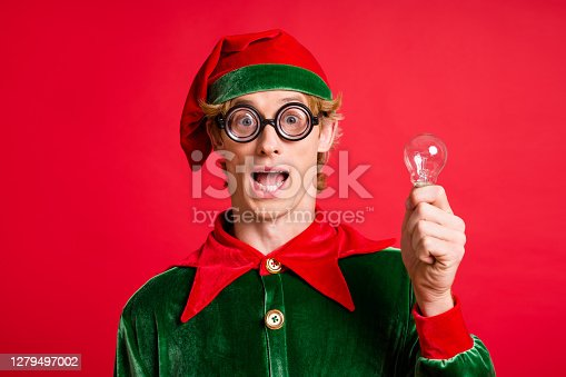 Creative thoughts concept. Excited crazy elf hold light bulb wear green cap costume isolated on red shine color background
