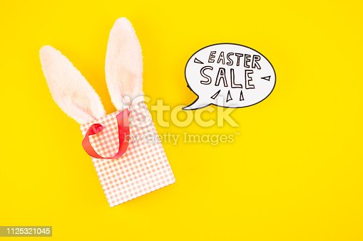 Creative Top view flat lay holiday promo composition Easter sale bunny ears eggs text message on bold yellow paper background copy space Template Easter day seasonal minimal concept