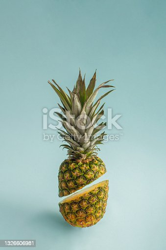istock Creative tropical fruit idea with cut raw organic pineapple on bright blue background. Minimalistic vertical arrangement, summer vibes and food concept. 1326606981