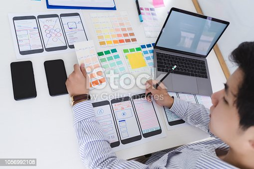 1182469817istockphoto Creative ux designer designing screens for mobile responsive website development with UI/UX. Developing wireframe sketch layout design mockup on smartphone screen. 1056992108