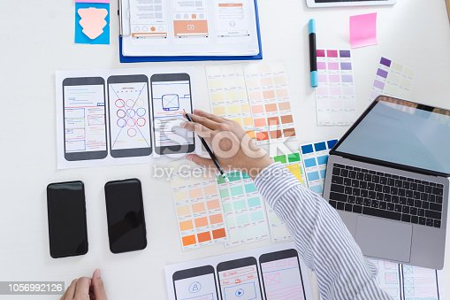 1182469817istockphoto Creative ux designer designing screens for mobile responsive website development with UI/UX. Developing wireframe sketch layout design mockup on smartphone screen. 1056992126