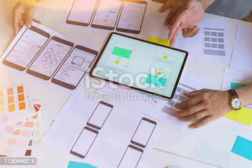 Creative ux designer hands sketching of screens for mobile responsive website development with UI/UX.