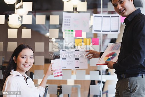 1182469817istockphoto Creative ux designer team developing wireframe sketch layout design mockup on smartphone screen. 1056991196