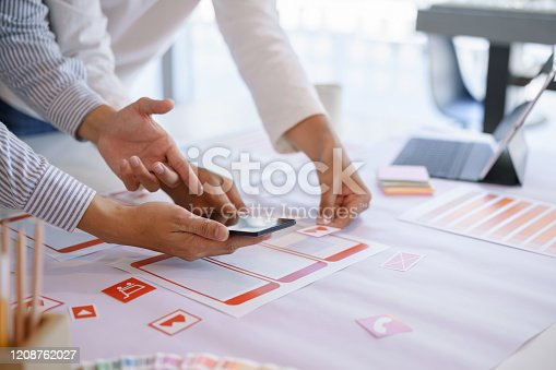 1182469817 istock photo Creative ux designer team discussing mobile app screen wireframes workflow. 1208762027