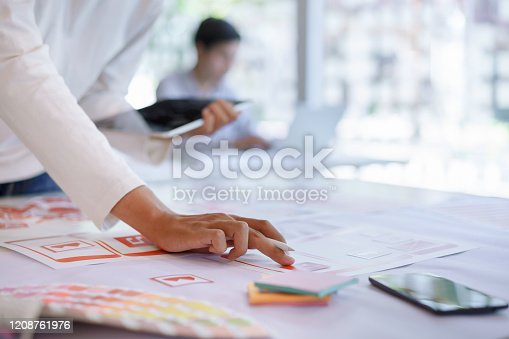 1182469817 istock photo Creative ux ui designers designing screens for mobile responsive website development with UI/UX. Developing wireframe sketch layout design mockup on smartphone screen. 1208761976