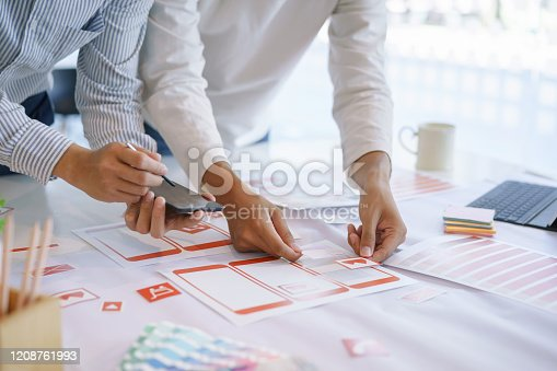 1182469817 istock photo Creative ux ui designers designing screens for mobile responsive website development with UI/UX. Developing wireframe sketch layout design mockup on smartphone screen. 1208761993