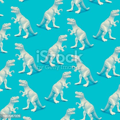 istock Creative white painted dinosaur pattern on blue background. Abstract art background. Minimal  concept for kids. 1007087026