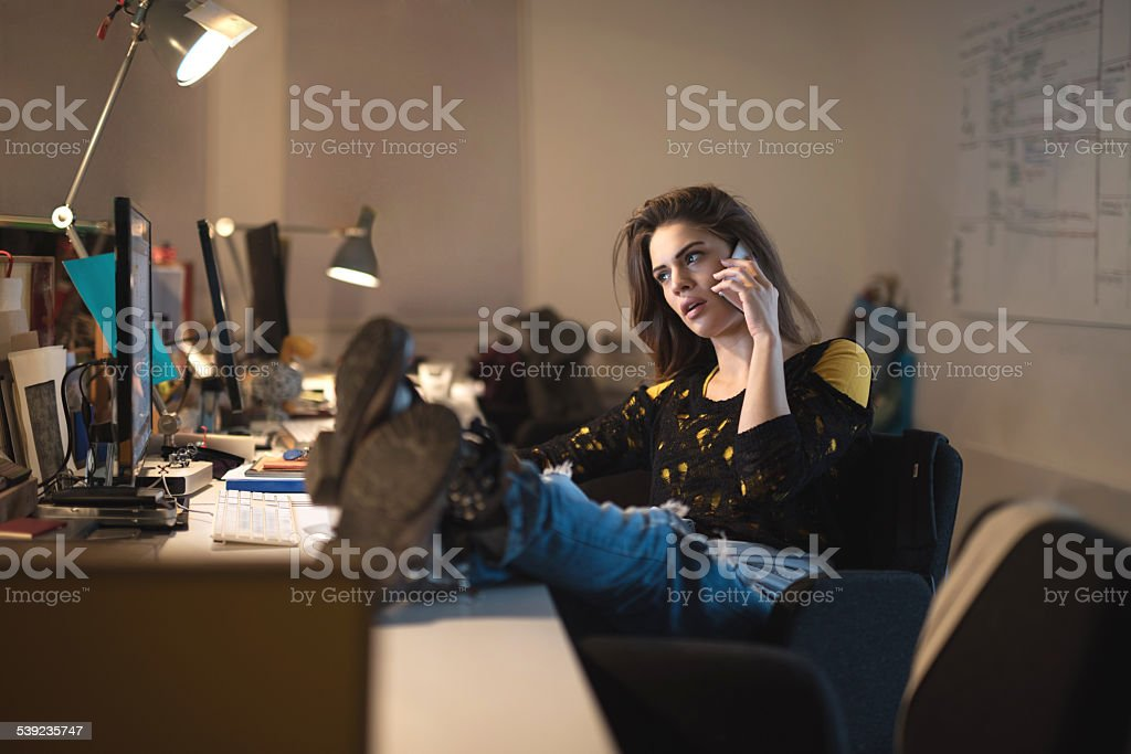 Creative woman talking on mobile phone in the office. royalty-free stock photo