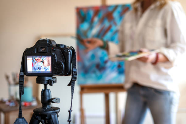 Creative woman vlogging her painting technique and skill stock photo