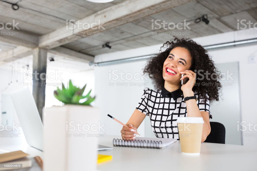 Creative woman working at her desk Creative woman sitting at the desk. Designer woman working in her office talking on mobile phone while making a sketches. 20-24 Years Stock Photo