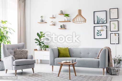 Creative, wooden pendant light above a gray sofa and a comfy armchair in a scandinavian living room interior with a gallery of botanic drawings