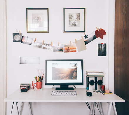 designer's workspace, computer on a white table, photographs hanging on the wall, vintage fashioned, framed paintings on the wall, editing of a photograph in progress on the screen.