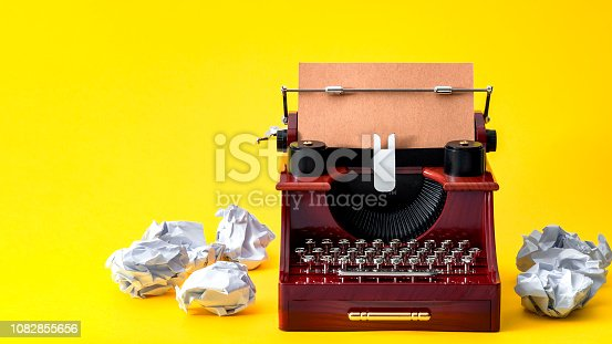 Creative writing, vintage technology and artistic pursuit concept with an retro typewriter surrounded by crumpled paper balls isolated on minimalist bright yellow background with copy space