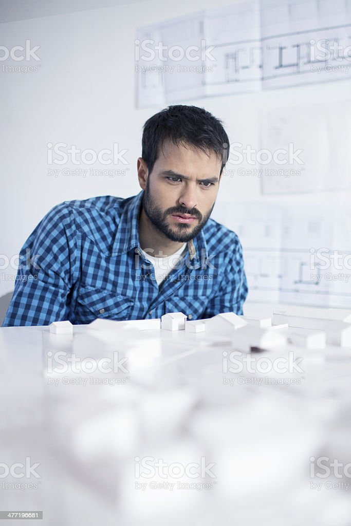 Architect working on an architectual model in the office.