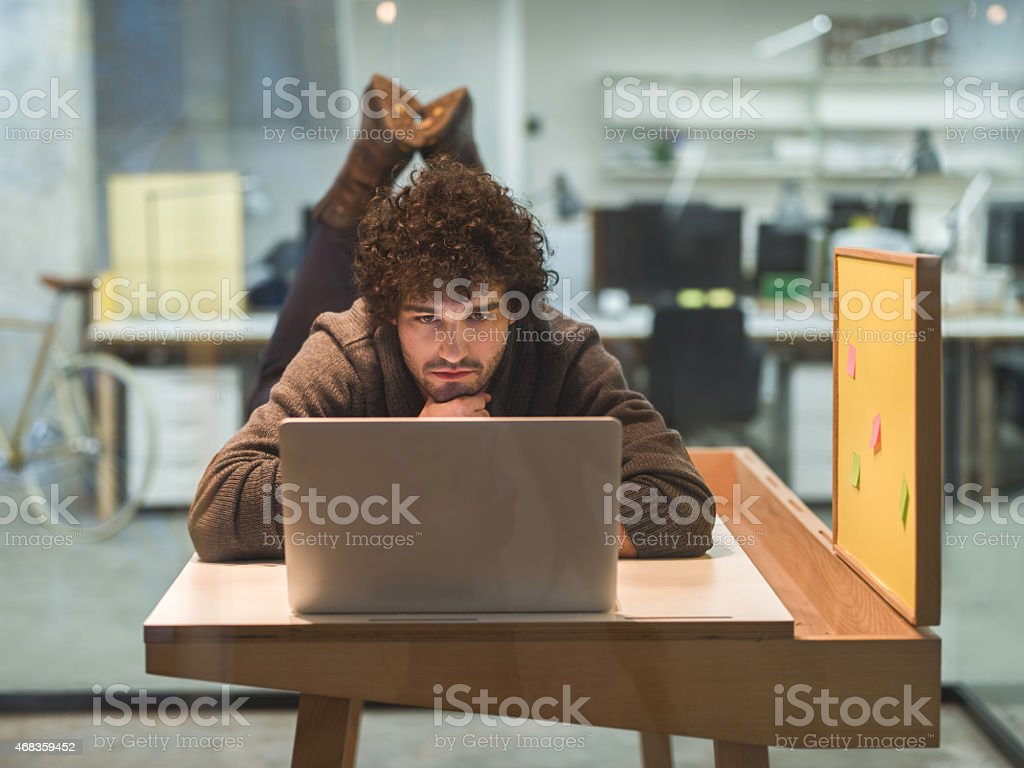 Creative young man using laptop in the office. royalty-free stock photo