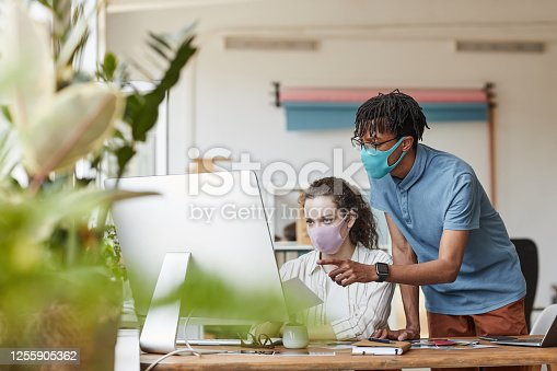 Portrait of two young photographers wearing masks while pointing at computer screen and reviewing pictures in office studio, copy space