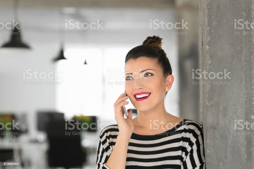 Creative young woman talking on phone in the office Happy creative young woman standing in the modern office and talking on phone. Adult Stock Photo