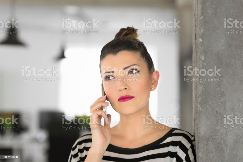 Creative young woman talking on phone in the office Happy creative young woman standing in the modern office and talking on phone. Close up of face. Adult Stock Photo