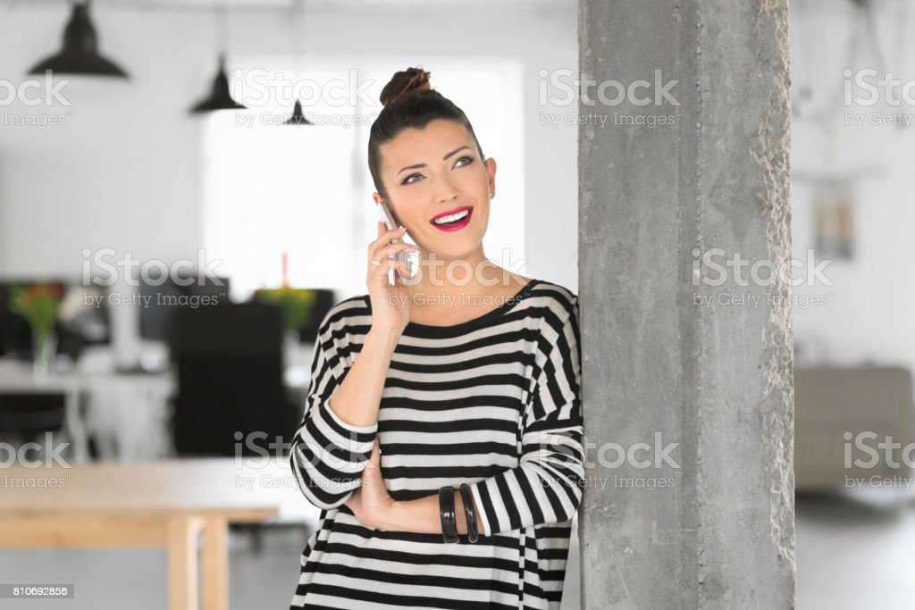Creative young woman talking on phone in the studio Happy creative young woman standing in the modern office and talking on phone. Adult Stock Photo