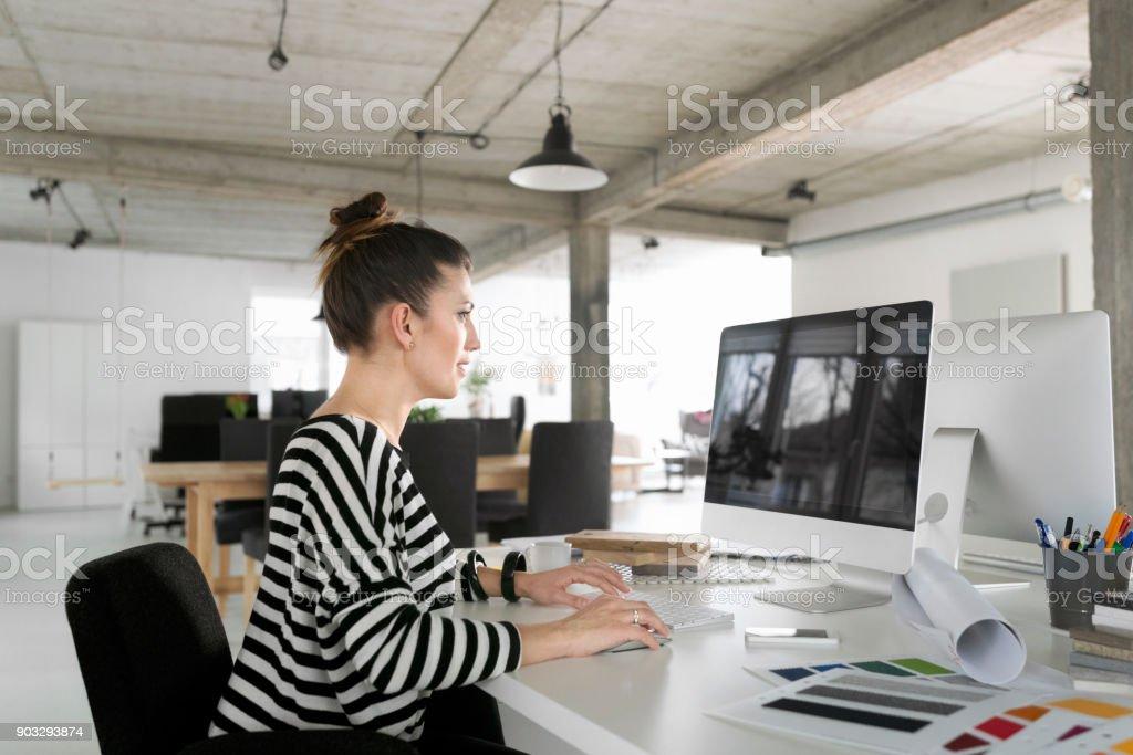 Kreative junge Frau, die mit Computer im studio – Foto