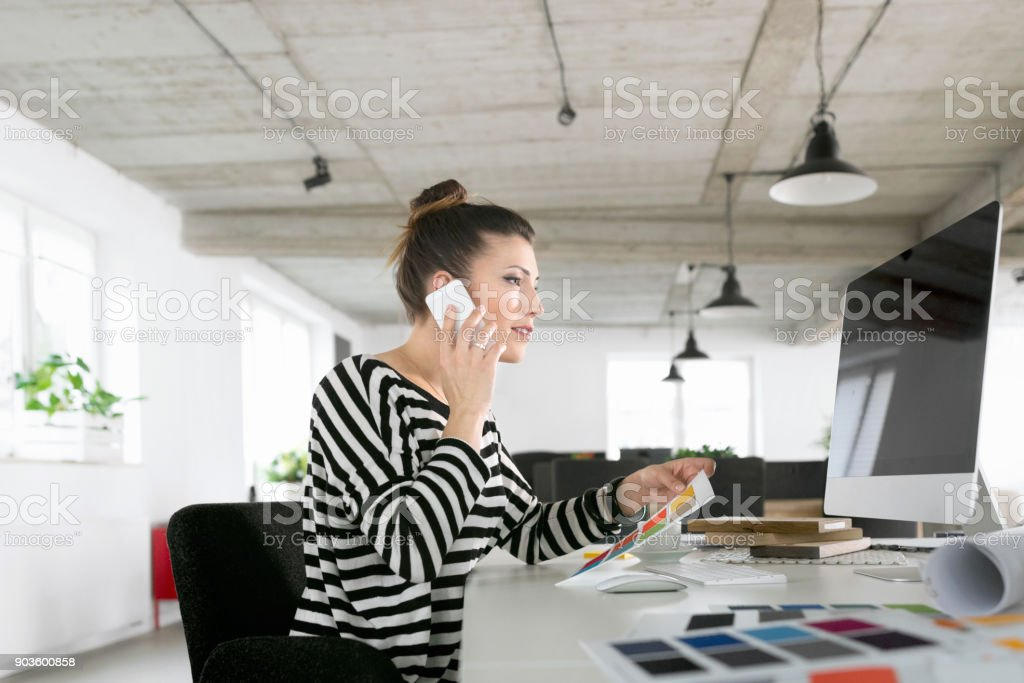 Creative young woman using computer in the studio Creative young woman working in the studio, sitting at the desk and using computer, holding color samples in hand and talking on phone. Adult Stock Photo