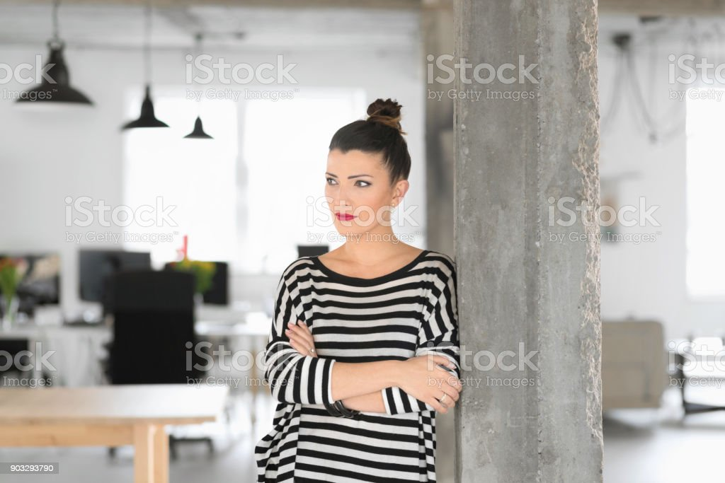 Creative young womanstanding in the modern office Creative young woman standing in the modern office with arms crossed. Adult Stock Photo