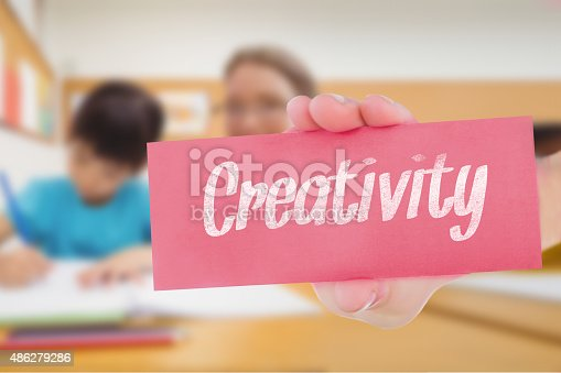 The word creativity and hand showing card against pretty teacher helping pupil in classroom